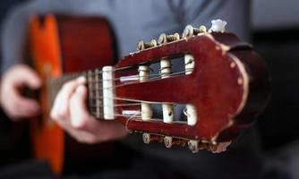 Guitarist's hand squeezes fingers on the chords of an acoustic guitar photo