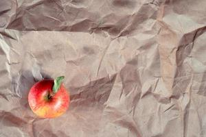 Red apple on crumbled craft paper
