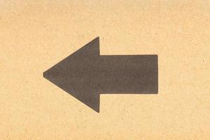 Flecha negra apuntando hacia la izquierda sobre fondo de cartón marrón foto