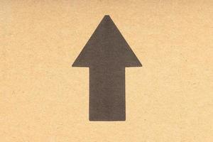 Flecha negra apuntando hacia arriba sobre fondo de cartón marrón foto