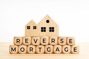 Palabras de hipoteca inversa sobre bloques de madera en la mesa foto