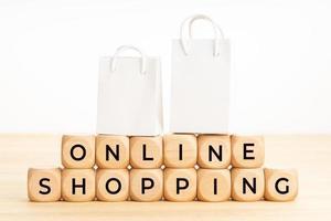 Texto de compras en línea sobre bloques de madera en la mesa y bolsas de papel. foto