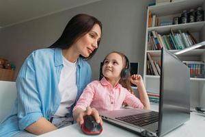 mamá ayudando a su hija con el aprendizaje virtual foto