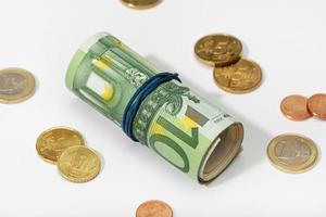 Rollo de billetes en euros con banda de goma y monedas aislado sobre fondo blanco. foto