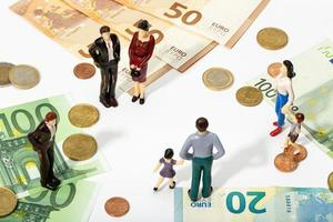 Figuras humanas mirando billetes y monedas. foto