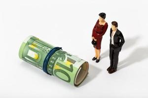 Human representation of a couple looking at a roll of euro banknotes photo