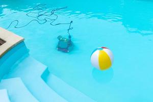Underwater robot cleaning a swimming pool and an inflatable ball floating photo