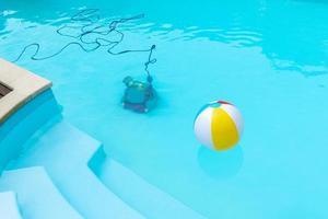 robot subacuático que limpia una piscina y una bola inflable flotante foto