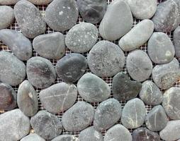 Gray sea pebble stone wall texture background photo