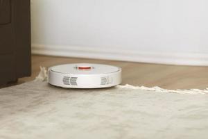 Aspiradora robótica blanca sobre una alfombra limpiando el polvo en el interior de la sala de estar. tecnología de limpieza electrónica inteligente. poca profundidad. foto