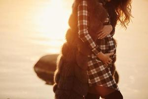 Pregnant woman in a beautiful dress. Focus on the abdomen. photo