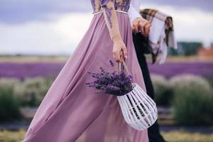 Beautiful young woman in a blue dress holds a bouquet of flowers lavender in a basket while walking outdoors through a wheat field at sunset in summer. Provence, France. Toned image with copy space