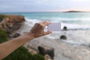 Female hand holding a white business card or sticky note with place for text on the beach background and the sea making waves. Selective focus photo
