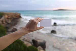 mano femenina sosteniendo una tarjeta de presentación blanca o una nota adhesiva con lugar para el texto en el fondo de la playa y el mar haciendo olas. enfoque selectivo foto