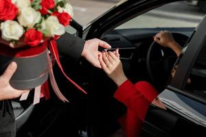 Polite man with a bouquet of flowers helping a businesswoman in a red suit to get out of a car parking outdoors photo