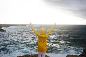 Young woman dressed in a yellow raincoat standing with outstretched arms while enjoying beautiful sea landscape on a rainy day on a rocky beach in cloudy spring weather photo