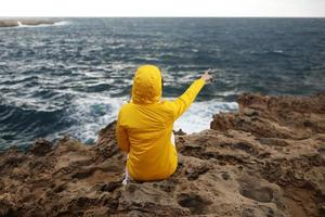 Young woman in a yellow raincoat is sitting on the cliff looking at big waves of the sea while enjoying the beautiful sea landscape on a rainy day on the rock beach in cloudy spring weather. photo