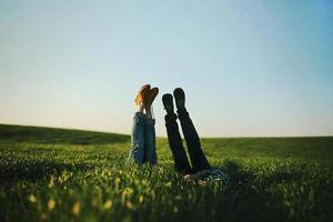 vista de las piernas de un hombre y una mujer que sobresalen de la hierba verde alta en un día de verano. enfoque selectivo. foto