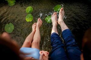 pareja chapoteando sus pies en el agua al atardecer foto
