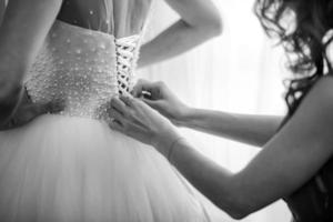 Bridesmaid helping bride fasten a corset and getting her dress ready, preparing bride in the morning for the wedding day. Bride's meeting
