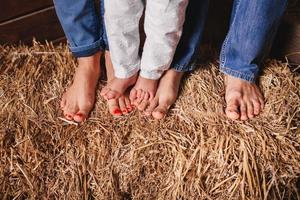 Bare feet of family members - mother, father, and baby in the hay.