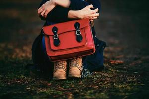 Stylish young girl in brown shoes and a warm coat sitting in the park with a red bag. photo