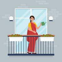 Indian woman watering flowers on balcony vector