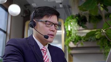 empresário usando fone de ouvido, falando com um chamador no departamento de atendimento ao cliente.