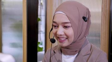 Woman in Hijab at the Computer with Headset on a Call video