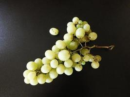 Green or yellow grapes on a black table background