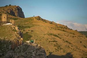 Vista de la fortaleza genovesa en la ladera de una montaña con un nublado cielo azul en Crimea foto