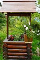 Wooden water well decorated with flowers in pots photo