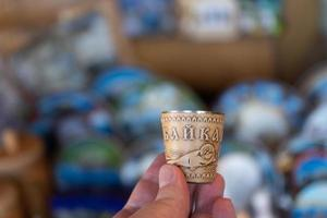 Hand holding a shot glass with the image of a seal on birch bark photo