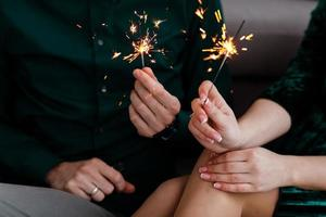 Male and female hands holding lit Bengal lights. Beautiful happy young family celebrating Christmas together. Couple holding Bengal lights. photo