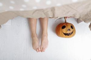 Legs of a little girl with a pumpkin are lying on the floor under the table