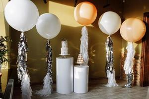 Decoration for birthday with a two-story cake and big white and beige balloons with tinsel. Candy bar with macaroon or macarons. Birthday party. Selective focus. photo