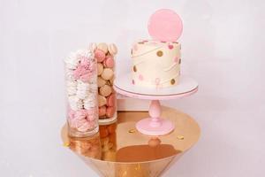 Beautiful birthday cake with pink decor for the birthday of a child. Candy bar with macaroons and marshmallows. photo