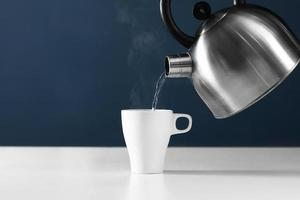 Kettle pouring boiling water into a cup with steam on wood table photo