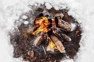 Campfire burns in the snow in the woods. Campfire burning in cold winter. Snow, forest and fire. Winter. Tourism. Flames on snow. Winter background. Nature. photo