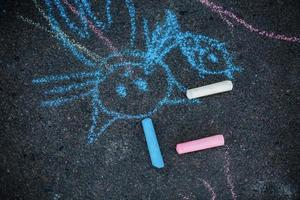 Drawing of cat chalk on the asphalt. Colorful chalk drawing on asphalt, funny cat. photo