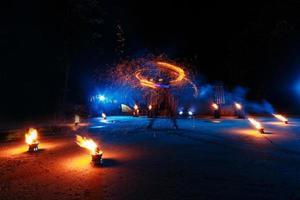 espectáculo de fuego, baile con llamas, maestro masculino haciendo malabares con fuegos artificiales, actuación al aire libre, dibuja una figura ardiente en la oscuridad, chispas brillantes en la noche. un hombre en un traje llevó a bailar con fuego foto