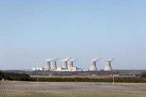 vista de una planta de energía nuclear. vista de las chimeneas humeantes de una planta de energía nuclear, líneas eléctricas y bosque, bajo un cielo azul con nubes blancas. foto
