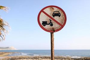 Old No Cars, No Motorbikes sign on the beach and blue sky background on sunny day. photo