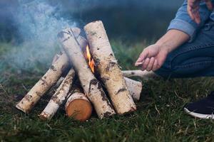 las manos del hombre encienden un fuego en las montañas. foto
