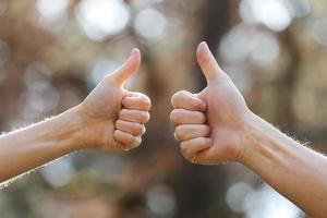 Male and female hands showing thumbs up outdoors. photo
