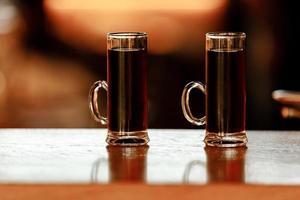 dos vasos de tragos alcohólicos en el bar. tiradores de mini cócteles sobre fondo de madera. foto