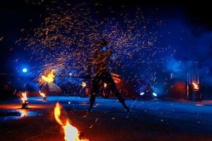 Fire show, dancing with flame, male master juggling with fireworks, performance outdoors, draws a fiery figure in the dark, bright sparks in the night. A man in a suit LED dances with fire photo