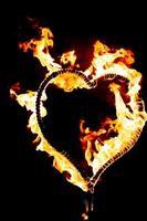 corazón ardiente con llamas. aislado sobre fondo oscuro. espectáculo de fuego por la noche. tarjeta de feliz dia de san valentin. Corazón ardiente de fuego de Bengala. espacio para texto. boda o concepto de San Valentín. Feliz año nuevo. foto