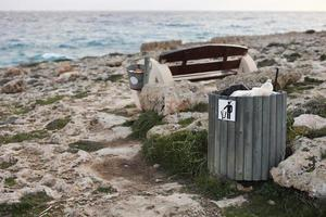 Full trash or litter bin with plastic bottle, beer cans, and organic waste visibly showing pollution in coastal areas near the sea. Wooden bench with bucket with garbage on rocky seashore.