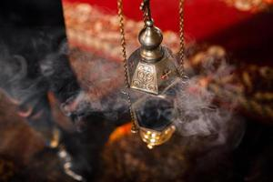A priest's censer hangs on an old wall in the Orthodox Church. Copper incense with burning coal inside. Service in the concept of the Orthodox Church. Adoration. photo
